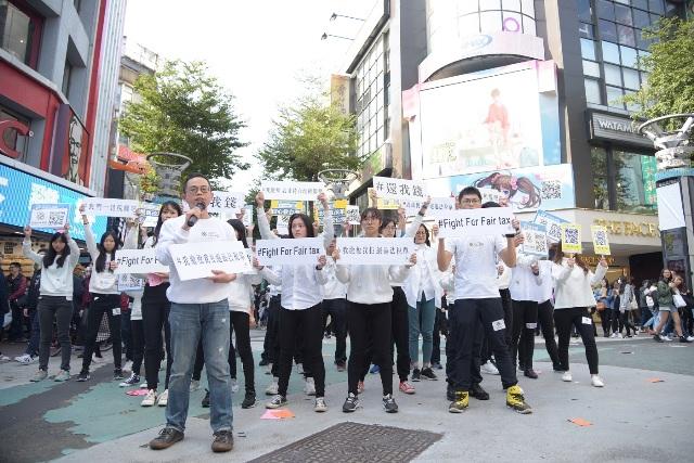 一群法稅改革聯盟青年志工在台北鬧區快閃,表達「我繳稅 我拒繳違法稅單」、youth unfriendly,呼籲政府正視稅制問題。