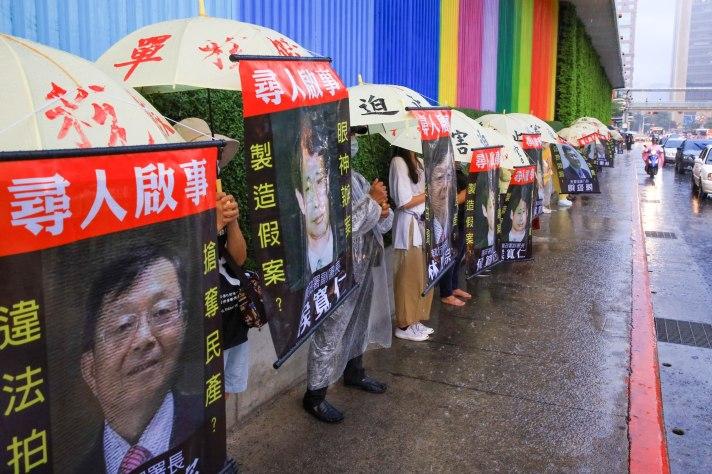 民團志工百米人龍在台北街頭壯觀排開,掛著執行署正副署長林慶宗、陳盈錦與前檢察官侯寬仁的人頭像,請全民一起幫忙協尋。