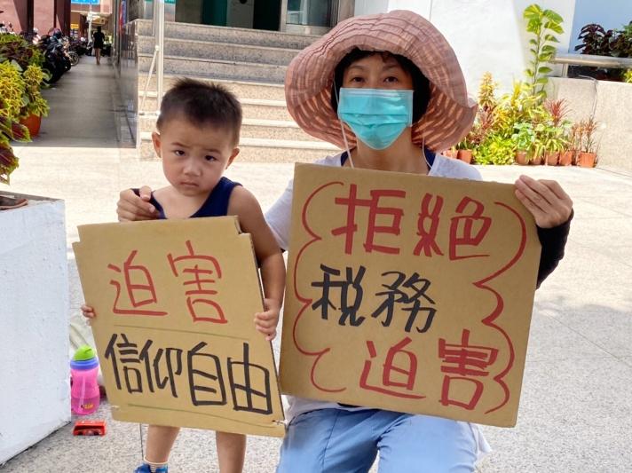 3歲黃姓小志工手持標語,站在抗議行列,對國稅局與行政執行署部分惡官,為了獎金不惜謊話連篇感到不恥。